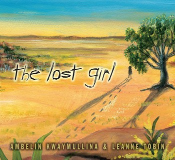 A girl and footsteps behind her walking in the desert by a tree